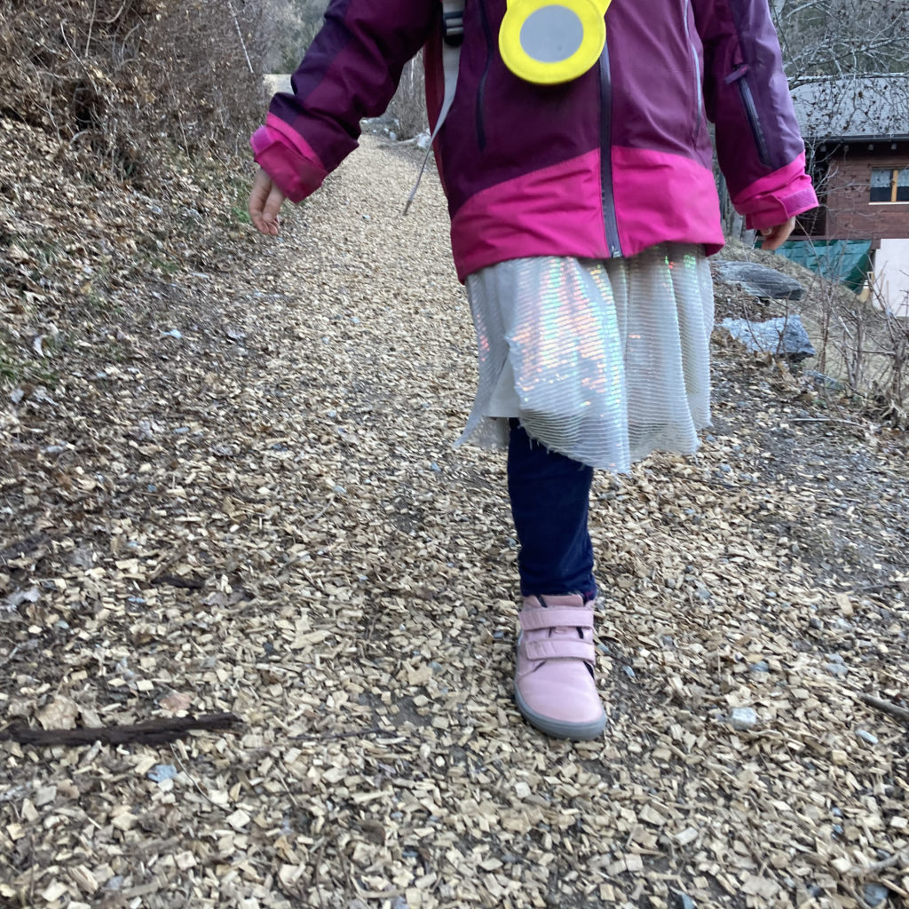 girl walking down hill wearing boots